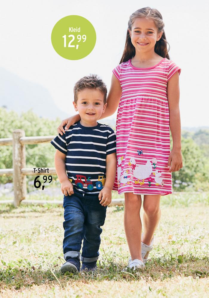 Mädchen steht mit kleinem Jungen auf dem Rasen